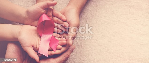 istock Family hands holding pink ribbon, breast cancer awareness, October pink concept 1169660478