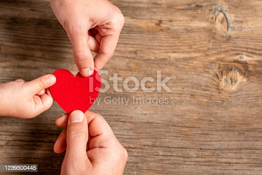 family hands holding red heart on wooden background. Love, Donation, charity, health concept
