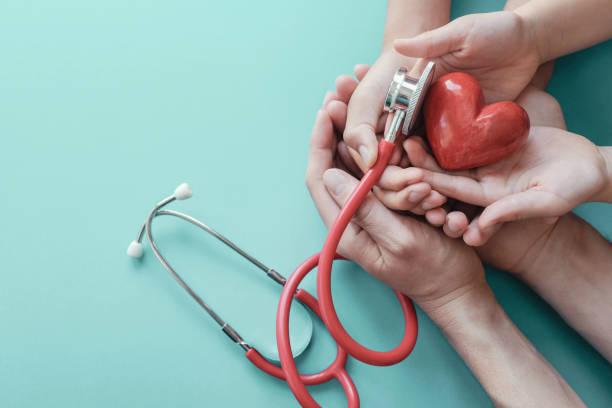 Familie Hände halten rotes Herz mit Stethoskop, Herzgesundheit, Krankenversicherung Konzept, Weltherztag, Weltgesundheitstag – Foto