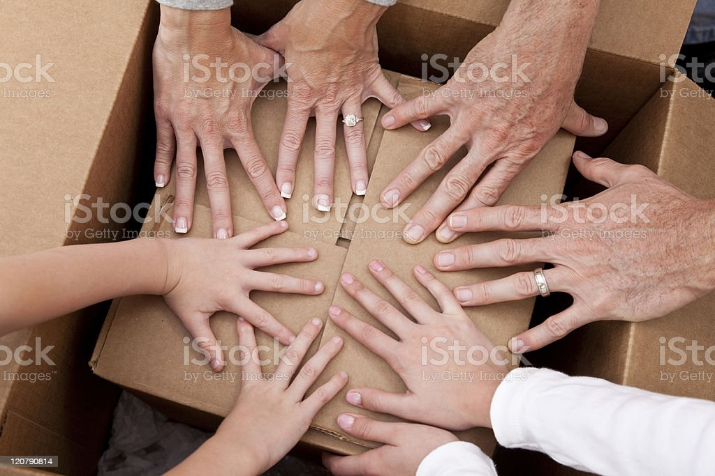 Family Hands Unpacking Boxes Moving House royalty-free stock photo