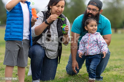 A Native American mom and dad hang out at the park and blow bubbles with their two young children on a warm summer afternoon.