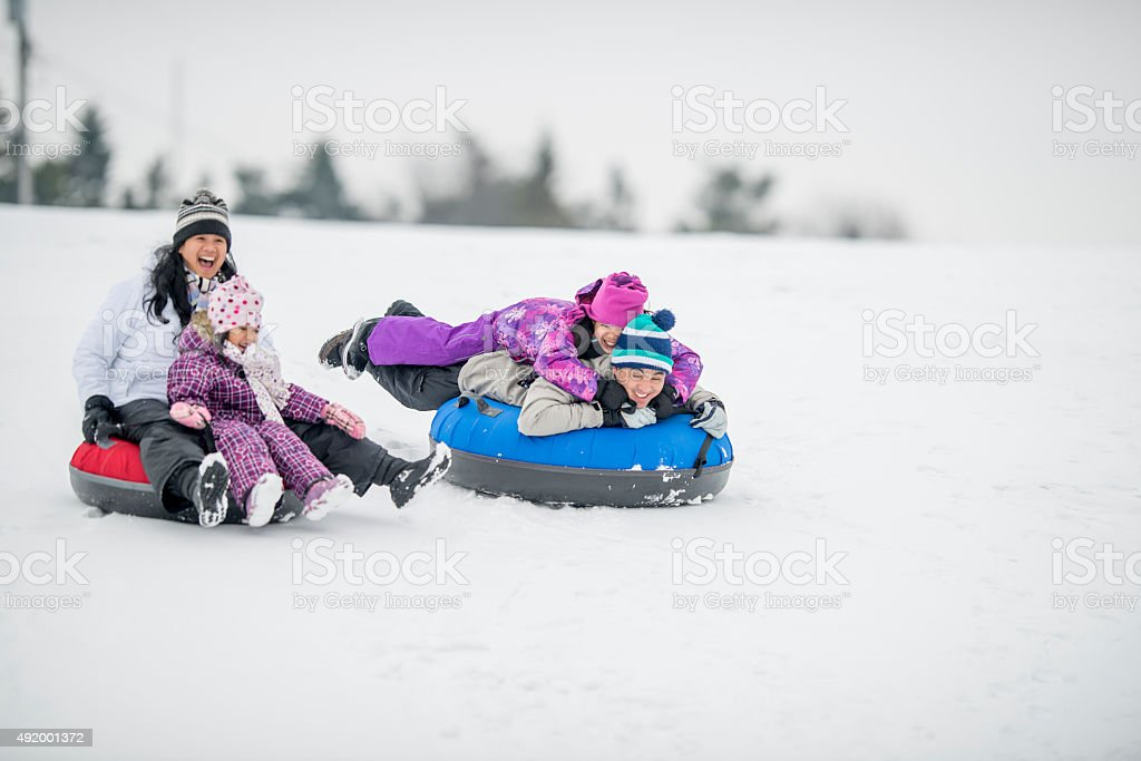 Family Happily Riding Inner Tubes Down a Snowy Hill stock photo