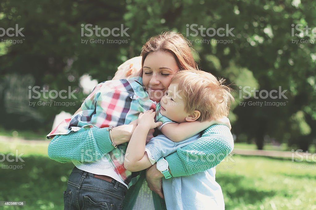 Family happiness! Happy mother tenderly embracing his two sons i stock photo