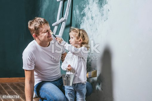 Family, happy daughter with dad doing home repair, paint walls, together with love