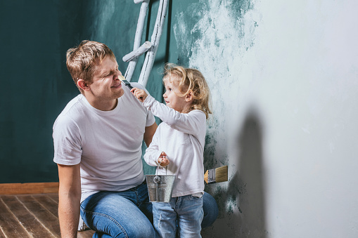 Family, happy daughter with dad doing home repair, paint walls,