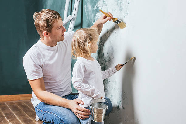 Family, happy daughter with dad doing home repair, paint walls, - Photo