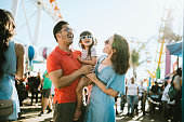 istock Family Has Fun at Outdoor Carnival Setting 1266364936