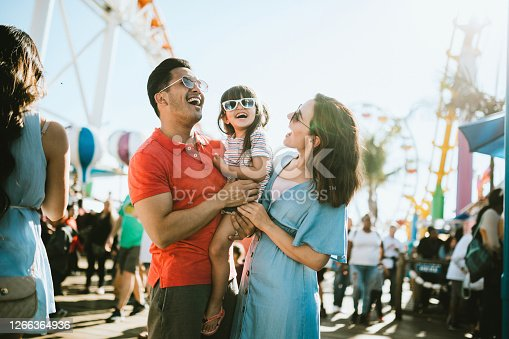 A cute mixed race family enjoys the rides and sun at the fair activities on Santa Monica Pier in Los Angeles, California.   They all wear sunglasses with big smiles.