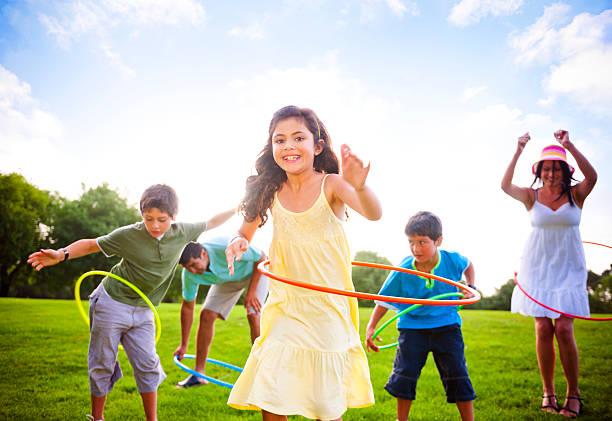 familie spaß zusammen im park - hula hoop workout stock-fotos und bilder