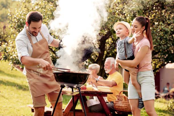 rodzina, która ma imprezę przy grillu w ogrodzie - grillowany zdjęcia i obrazy z banku zdjęć