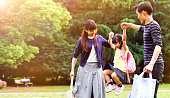 Family having a walk outdoors in summer in park, Tokyo, Japan. Parents are throwing their little daughter in the air in a playful way.