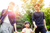 Family having a walk outdoors in summer in park, Tokyo, Japan. Parents are throwing their little daughter in the air in a playful way. Image is taken during Tokyo Istockalypse 2015