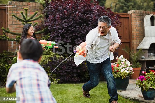 istock Family Having a Water Fight 928430372