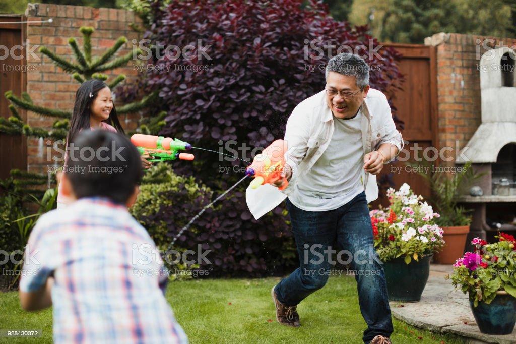 Famille ayant un combat de l'eau - Photo