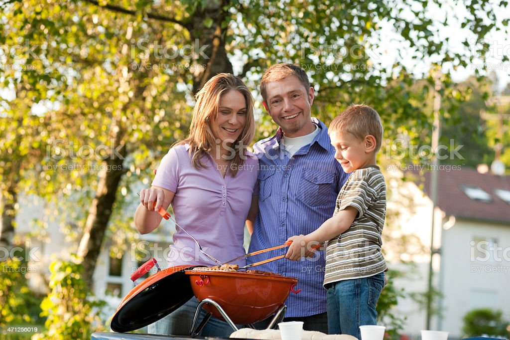 Family having barbecue in front of home royalty-free stock photo