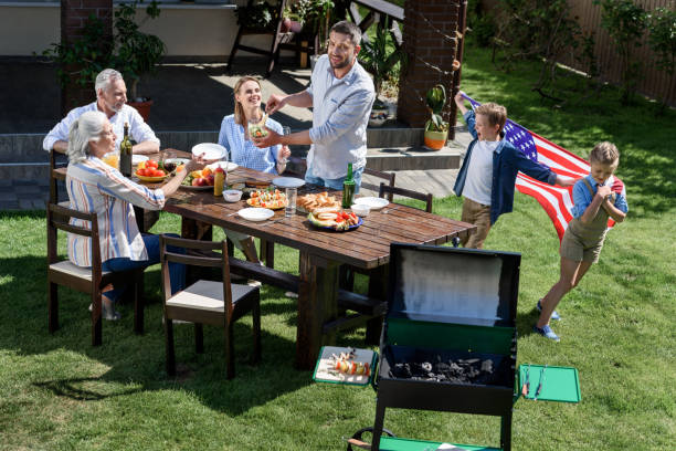 family having barbecue while celebrating 4th july together, Independence Day concept family having barbecue while celebrating 4th july together, Independence Day concept family 4th of july stock pictures, royalty-free photos & images