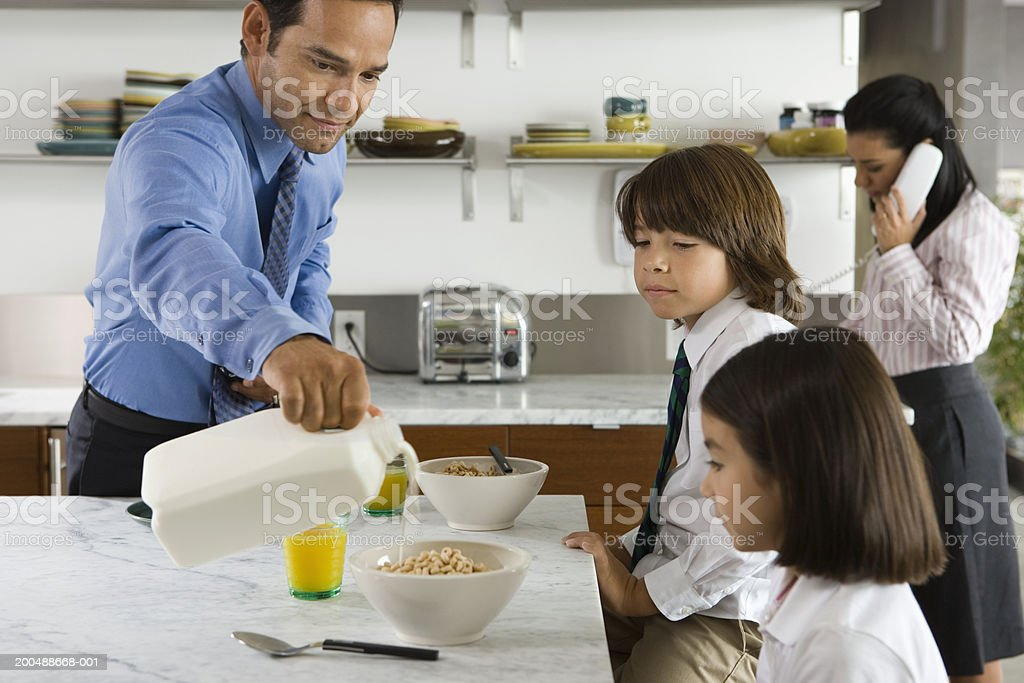 Family having breakfast, father pouring milk over cereal royalty-free stock photo