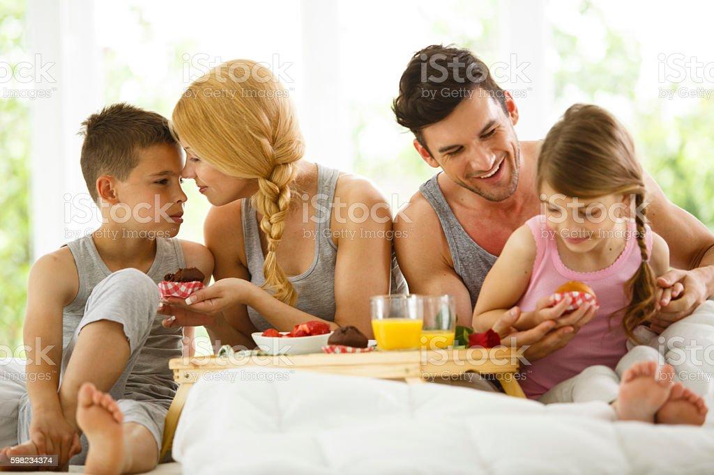 Família tomando café da manhã na cama foto royalty-free