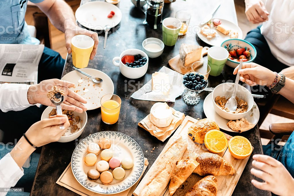family having breakfast together at weekend stock photo