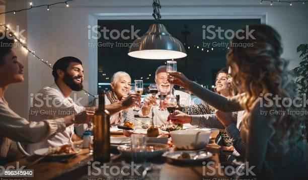 Family Having Dinner On Christmas Eve - Fotografie stock e altre immagini di 60-69 anni