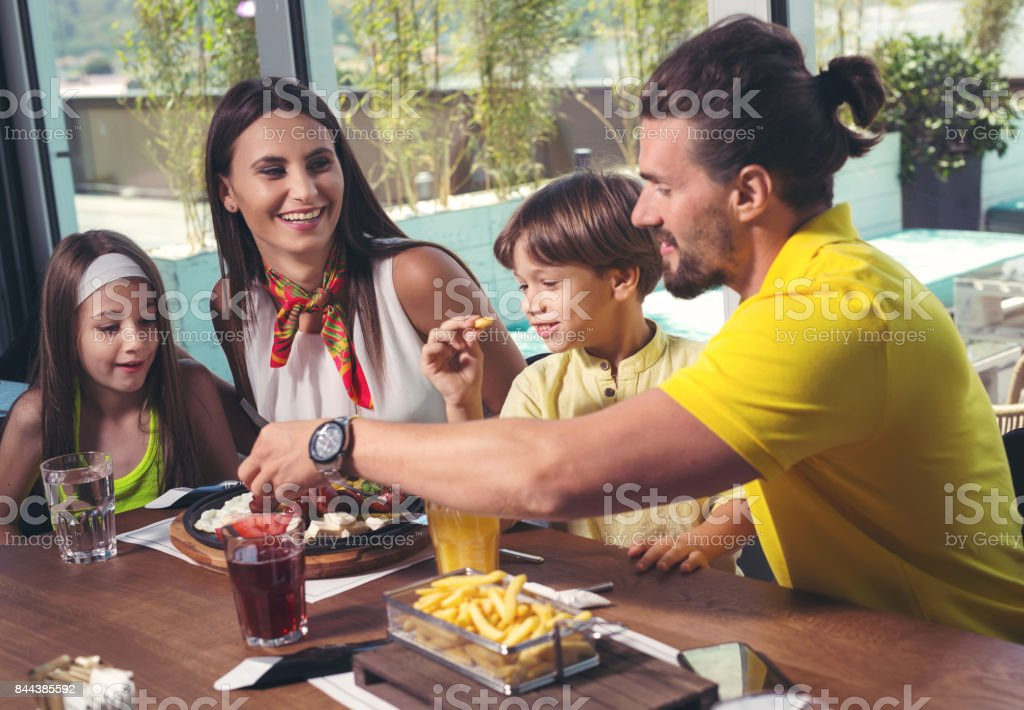 Family having enjoyable lunch at a restaurant. stock photo