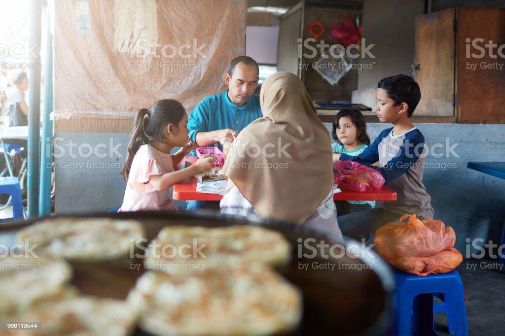 Familjen att ha mat på restaurang efter shopping - Royaltyfri 10-11 år Bildbanksbilder