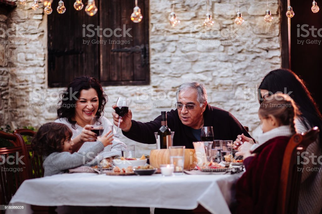 Family having fun and toasting with drinks at dining table stock photo