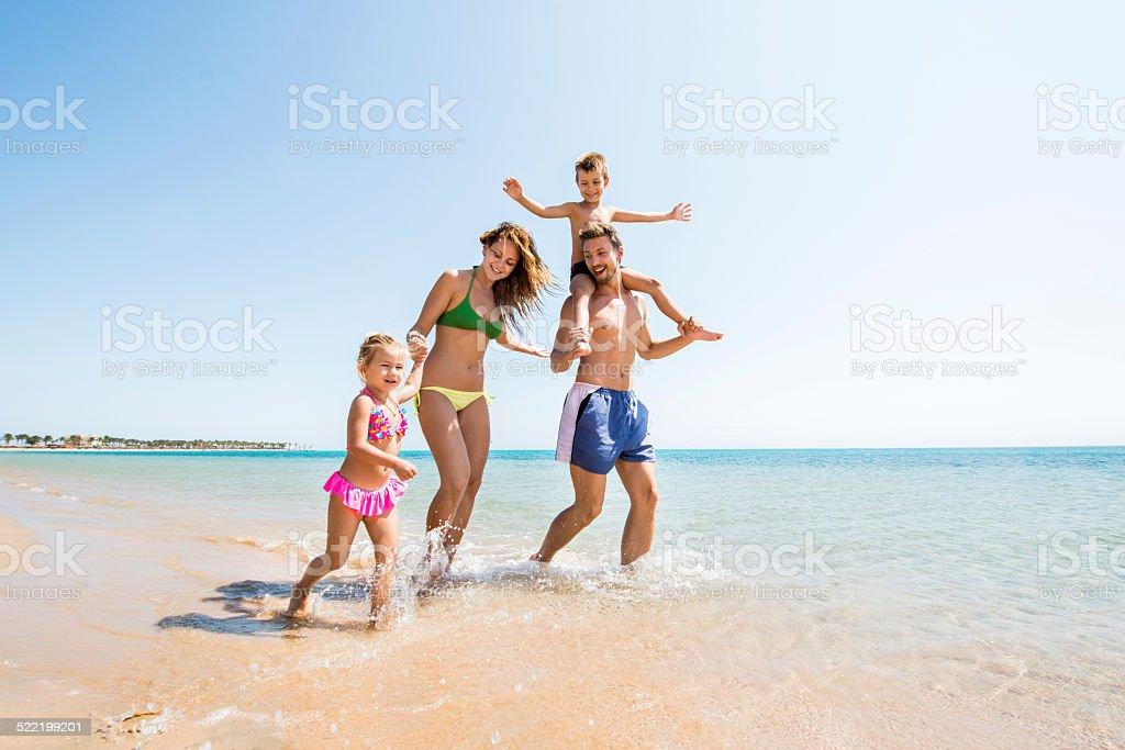 Family having fun at the beach. stock photo