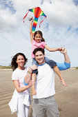 Family Having Fun Flying Kite On Beach Holiday Smiling To Camera