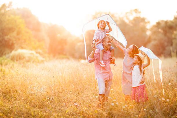 Family having fun flying kites stock photo