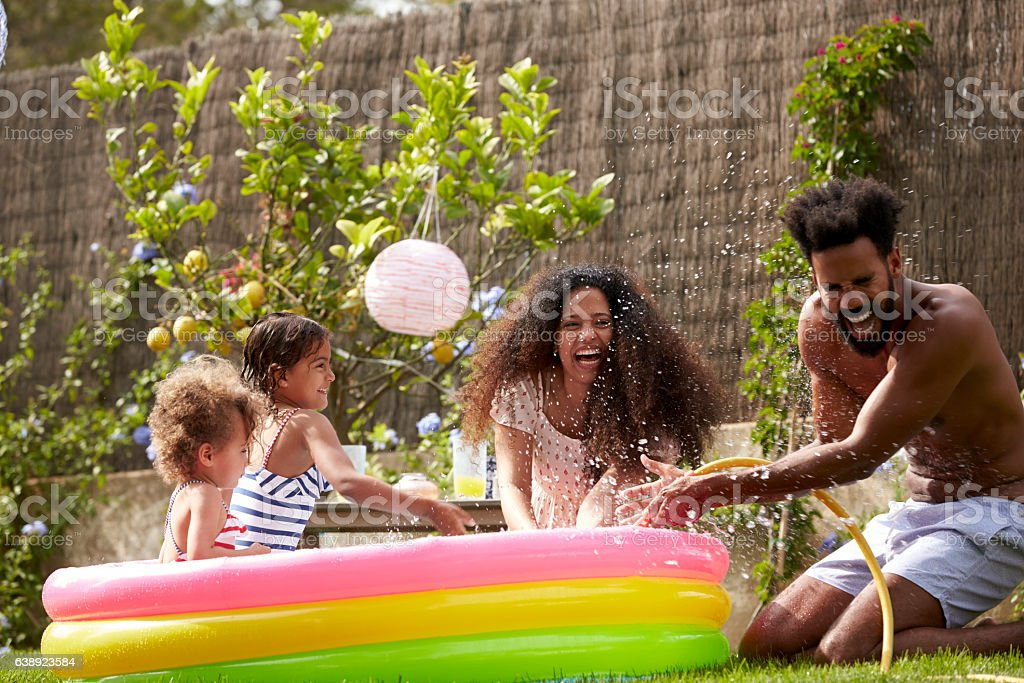 Family Having Fun In Garden Paddling Pool stock photo
