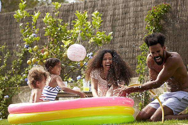Family Having Fun In Garden Paddling Pool Family Having Fun In Garden Paddling Pool backyard pool stock pictures, royalty-free photos & images