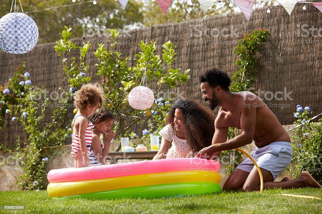 Family Having Fun In Garden Paddling Pool stock photo