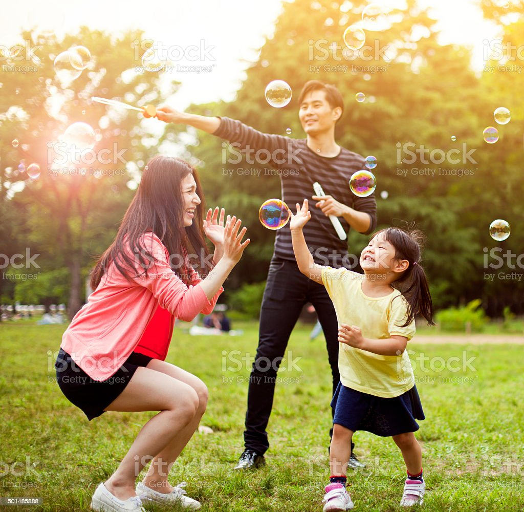 Family having fun in park with Soap Bubbles stock photo