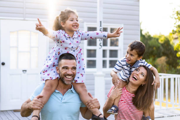 Family having fun in piggyback ride in front of house