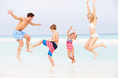 Family Having Fun Playing In Sea On Beach Holiday