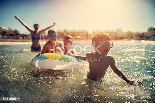 Little boy aged 7 having fun at sea with his family. Family is having great time todether. Candid smile and laughter. Sunny summer vacations day at sea. Costa del Sol, Andalusia, Spain.