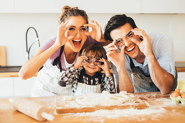 Family having fun in the kitchen Young family holding cookie cutters in front of their eyes while making cookies in the kitchen. cookie cutter stock pictures, royalty-free photos & images
