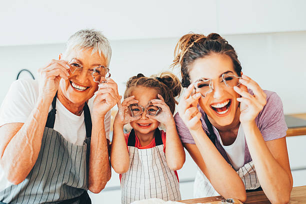 Family having fun in the kitchen Family holding cookie cutters in front of their eyes while making cookies in the kitchen. cookie cutter stock pictures, royalty-free photos & images