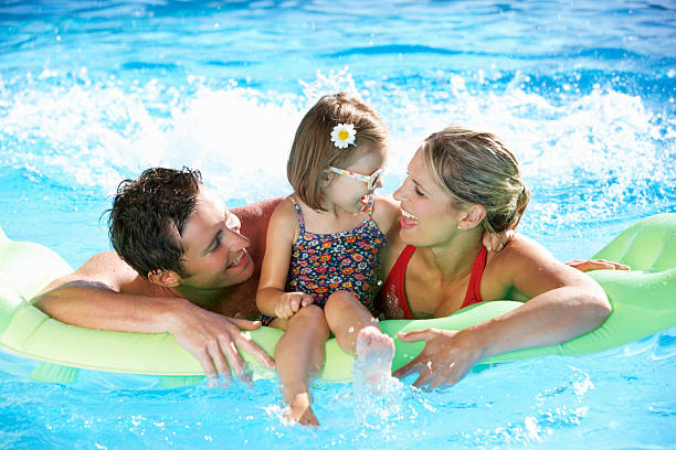 A family having fun in the swimming pool stock photo
