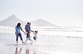 Shot of a young african family walking together in water at the beach