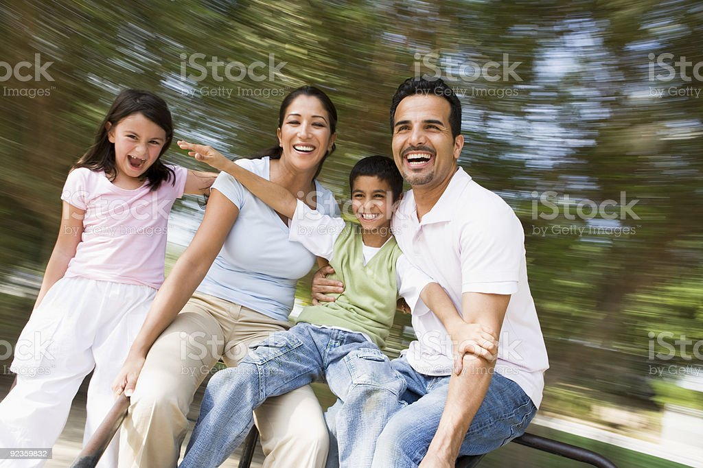 Family having fun on spinning roundabout royalty-free stock photo