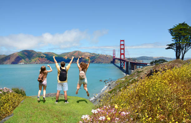 Family having fun on summer vacation trip. People with hands up jumping  and having fun on the top of the mountain, enjoying Golden Gate Bridge view. Family vacation  on California coast.. San Francisco, California, USA . san francisco bay stock pictures, royalty-free photos & images