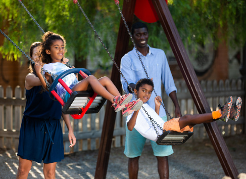 Friendly interracial family with two children having fun on swing on summer day