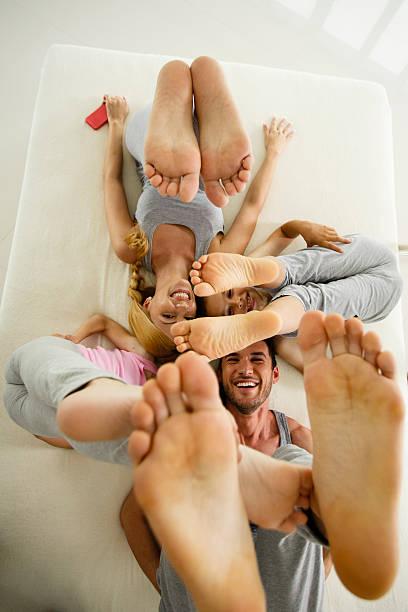 Familia divirtiéndose en la cama, Elevación de piernas - foto de stock