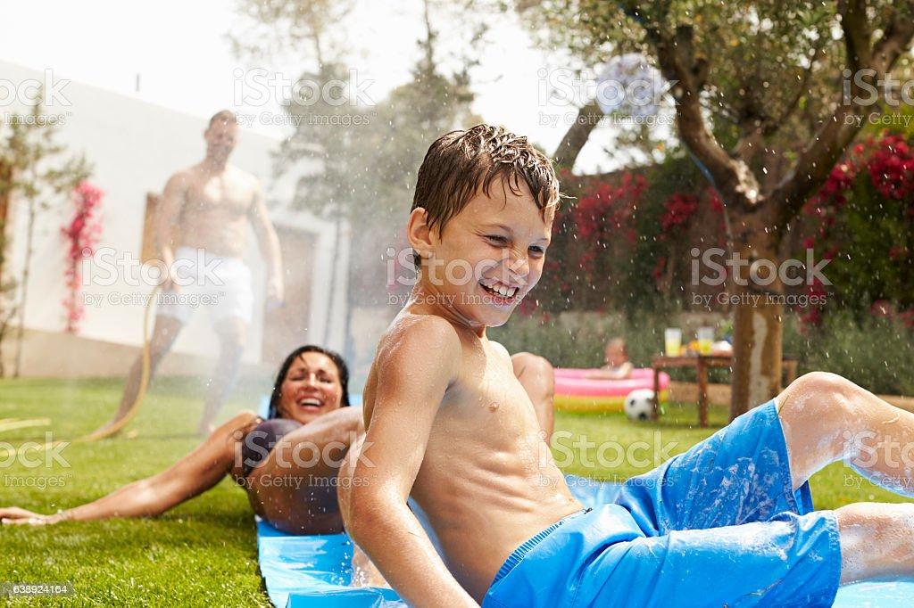 Family Having Fun On Water Slide In Garden stock photo