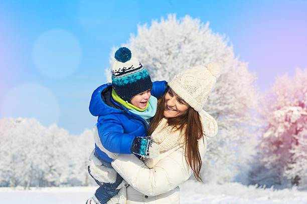 Family having fun outdoors in winter snowy and sunny day stock photo