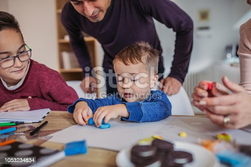 Group of people, two parents with two sons, doing homework all together at home