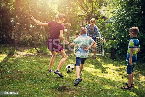 Mother and kids playing soccer in the garden. Spring or summer day.  Nikon D810