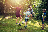 Family having fun playing soccer in the garden